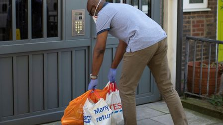 First Love foodbank co-founder Aerold Bentley leaving food outside entrance of flats in Poplar durin