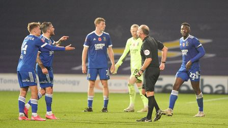 Referee Andy Haines goes for his yellow card as James Norwood continues to argue over Portsmouths co