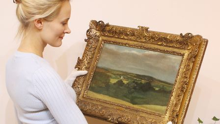 Sylvia Ewen, from Sworders' paintings department, holding the undiscovered John Constable painting o