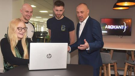 Group of workers smiling at a laptop