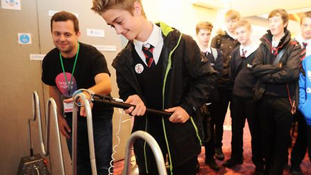 Suffolk Skills Show 2015 at Trinity Park, Ipswich. A student has a go at one of the exhibitions provided by Flow Energy