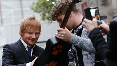 Singer Ed Sheeran signs a guitar as he arrives for the world premiere of his concert film, Jumpers For Goalposts, at the...