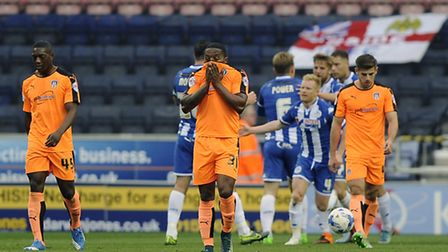 Despondent U's players after Will Grigg scores the fourth goal for Wigan against Colchester on Saturday