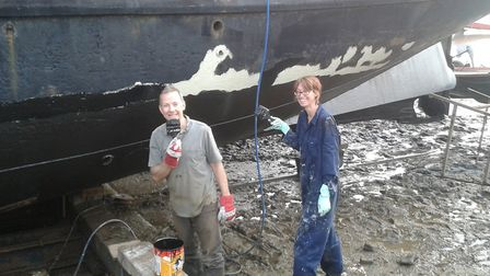 Gary and Bev giving the boat's underside a quick lick of paint Picture: Bev Rogers
