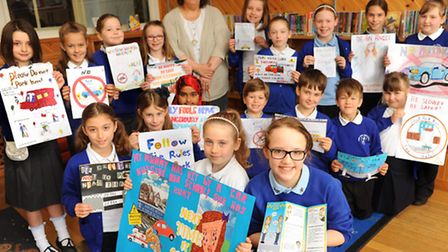 Children from Angel Road Junior School with their winning road safety posters, and governor Julie Br