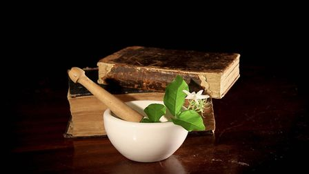 Old recipe books with herbs in a pestle and mortar