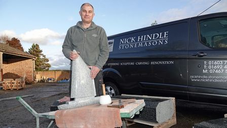 Stone mason Nick Hindle with the granite wherry sculpture which will top the new village sign for Wroham in the Norfolk...