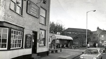 Black and white photo of city centre pub with old car outside