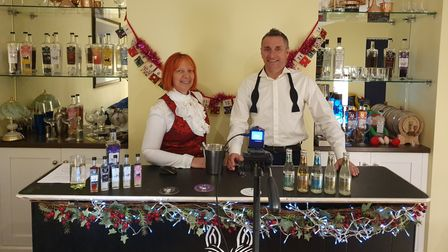Couple standing behind a gin with gins and tonics on display