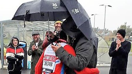Littleport runner Karen Wells is hugged by her husband Jamie after completing the London Marathon distance, Pictures: Lyn...