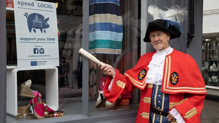 Great Dunmow town crier Richard Harris points to the sign urging residents to spend local, and support the town. Picture...