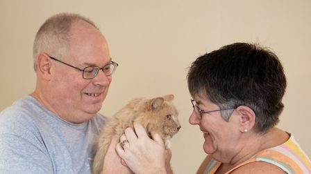 Keith, 53, and Su Bigland with his late mother's beloved pet cat, Biscuit, known as Bikkit, who has returned home after...