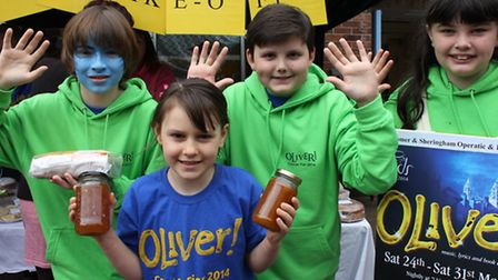 Young Oliver chorus members selling cakes at Cromer and Sheringham Operatic and Dramatic Society's o