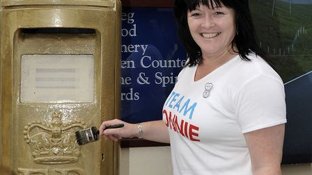 Jonnie Peacock's mum, Linda Roberts, painting the postbox gold in 2012. Picture: ARCHANT