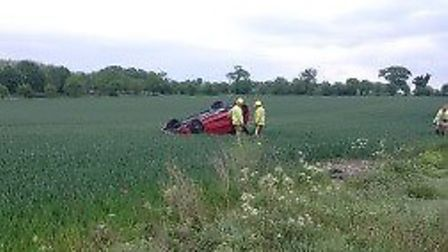 The car on its roof in a field at Buxton, near Aylsham. Picture: EAST OF ENGLAND AMBULANCE SERVICE T