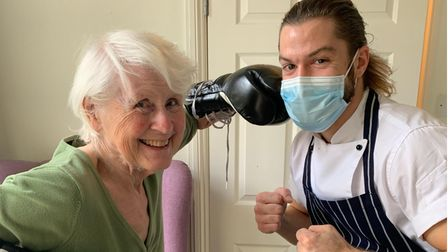 A resident at Carleton House Care Home pretending to be boxing with chef Rylan Charlton, who is also a professional boxer