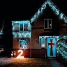 A house lit up with white, sparkly Christmas lights and a bow tie front door