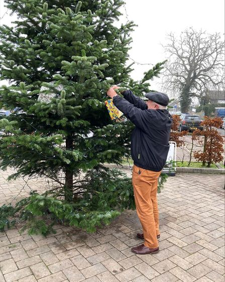 Great Dunmow mayor Mike Coleman dresses the Christmas tree with a festive parcel. Picture: SUPPLIED