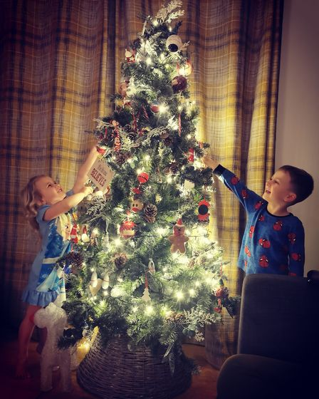Finley and Isla Goffin adding the last decorations to their Christmas tree