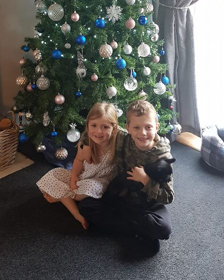 Evelyn and Jacob holding their dog, Nelly in frontof the Christmas Tree