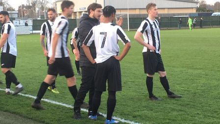 Woodbridge Town players take a rest during a time-out for an injury at Wellingborough Town. Picture: CARL MARSTON