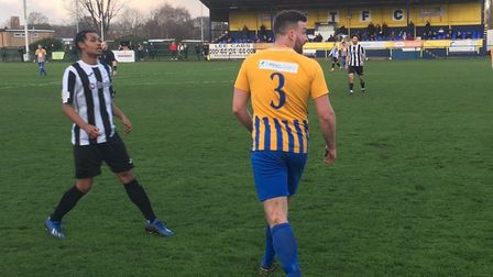 Woodbridge Town's Kyron Andrews, left, keeps close to Wellingborough left-back Liam Tuck. Picture: CARL MARSTON