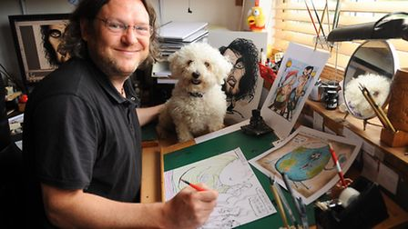 Cartoonist Brian Adcock in his studio at home at Sprowston, with his four-year-old dog, Millie. Pict