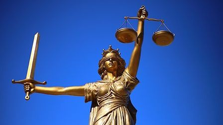 Lady Justice statue wearing a blindfold and carrying a beam balance and sword