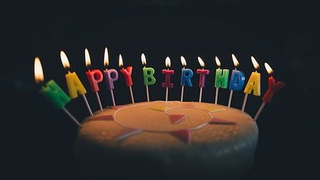 A chocolate birthday cake with lit candles that spell happy birthday