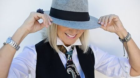 A woman wears a shirt, tie and trilby hat