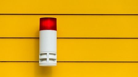 A home security alarm with a flashing red light on a yellow wall
