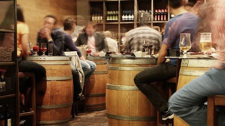 Drinkers are seating at beer barrels in a pub