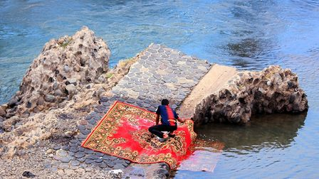 A man washes a red rug over rocks in a flowing river
