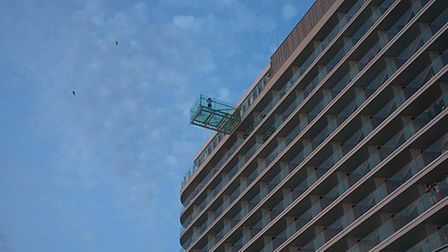A window cleaner cleans a skyscraper's top floor windows from a safety cage