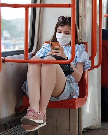 A young woman sits on a bus seat wearing a face covering and looking at her phone