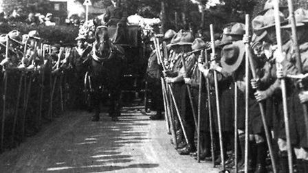 The sea scout funeral procession approaches Carlton Colville St Peter's Church with the route lined