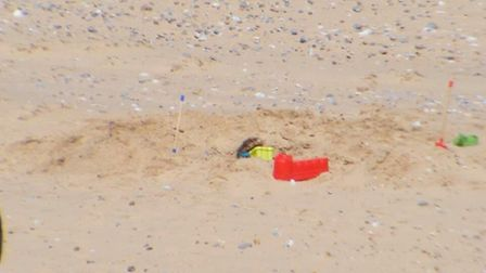 A girl inside a dangerously deep hole on Caister beach that prompted Coastwatch to intervene.