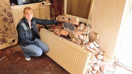 Tracy Dickinson inside her front room after a car crashed through the front wall of her home on Beva