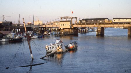 """The abandoned fishing vessel """"Yellowtail"""" is in the foreground, as the train from London crosses Oul"""