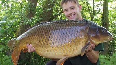 Jack Perkins proudly shows off a magnificent 36lb 4oz Fenn Lake record common carp taken on his f