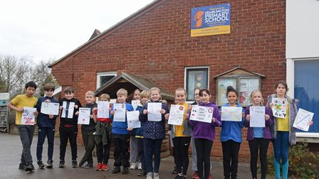 Year 6 pupils from Hemblington Primary School holding the signs they have made to back a 20mph speed