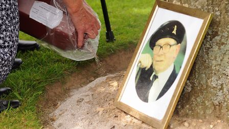 The Norfolk veterans visit Hottot-les-Bagues Cemetery, for a service. Jean and Kitty Burge scatter t