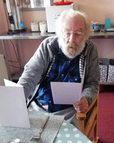 A resident at Bungay House reading Christmas cards made by Woodton Primary.