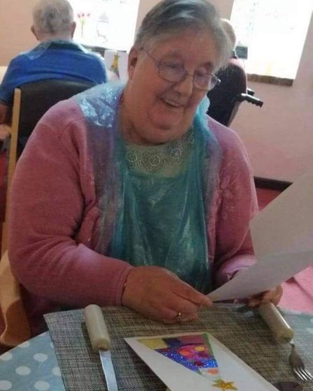 Residents at Bungay House open cards from Woodton Primary School.