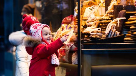 Children window shopping on traditional Christmas market in Germany on snowy winter day.