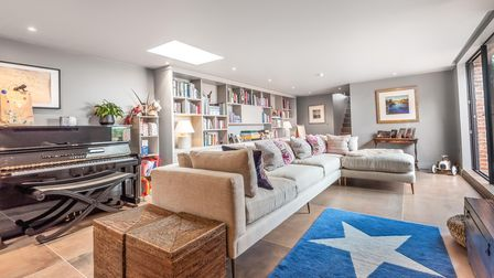 Cosy living room with corner sofa, piano and bookshelves in the background