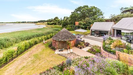 Thatched round house in cottage style garden with river and fields in the distance