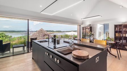 Modern kitchen island with sink overlooking the river and thatched round house outside