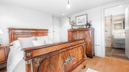 Large wooden double bed in contemporary bedroom with white walls and wood floors