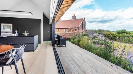 Contemporary kitchen with big sliding doors opening out on to a terrace surrounded by flowers